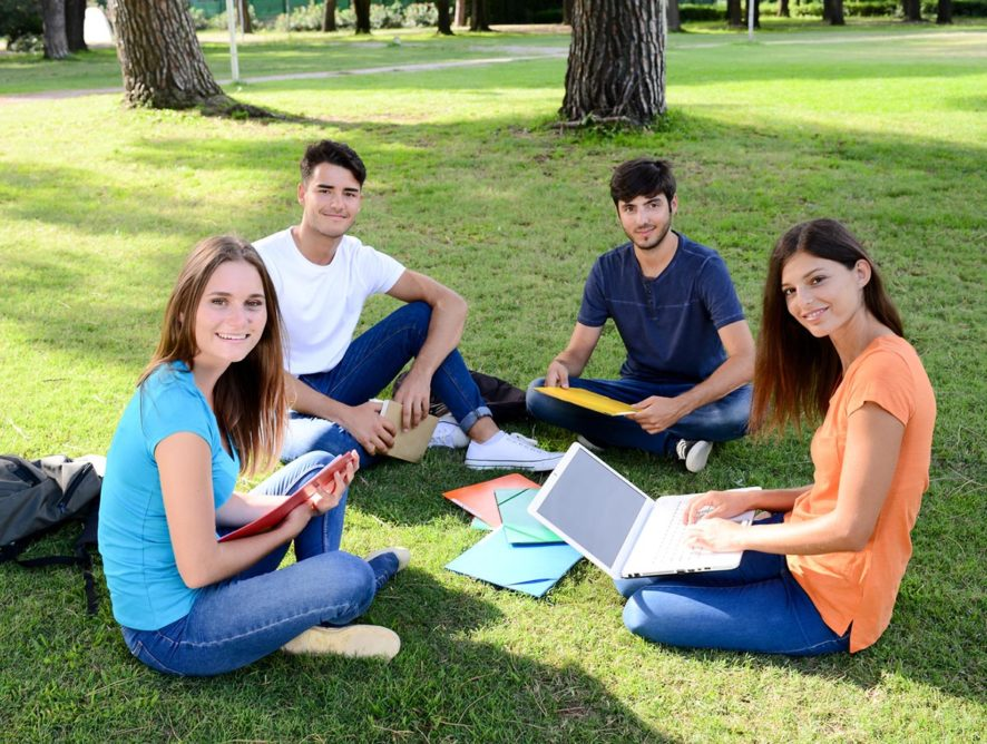 group of young students sitting together on green lawn of high school university campus
